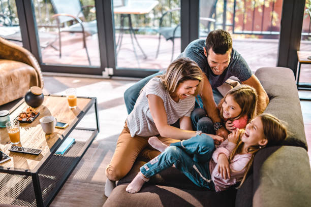 above view of playful parents tickling their daughters at home. - casa imagens e fotografias de stock