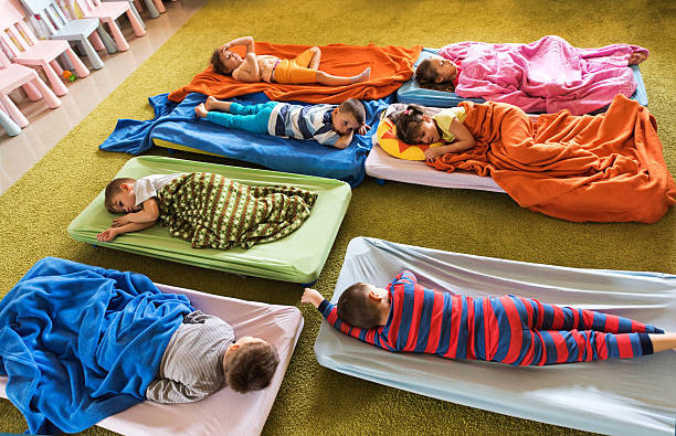 above view of preschoolers in pajamas sleeping at kindergarten. - napping stock photos and pictures
