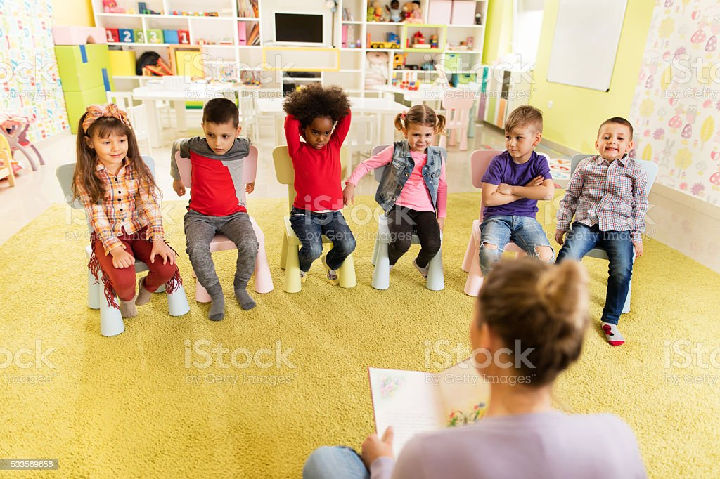 Above view of preschoolers listening a story at kindergarten. stock photo