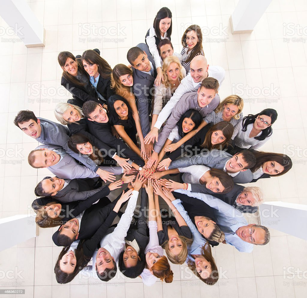 Above view of smiling business people joining hands in unity. royalty-free stock photo