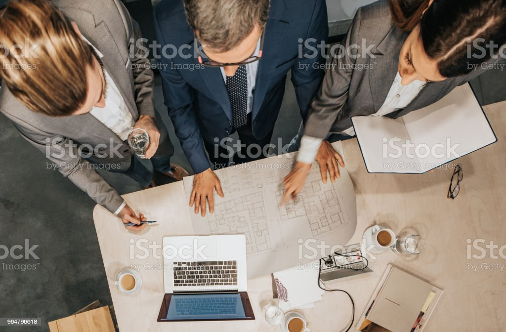 Above view of team of entrepreneurs analyzing blueprints in the office. royalty-free stock photo