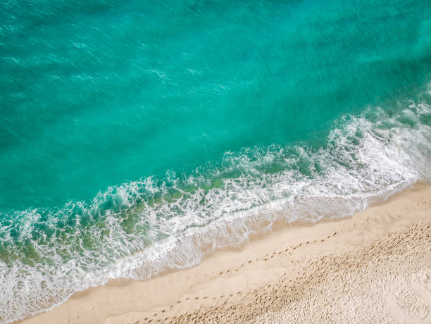 Above view of the turquoise mediterranean sea hitting the beach. stock photo