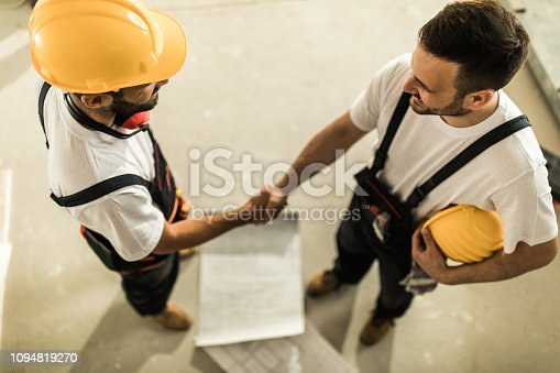 961745166istockphoto Above view of two manual workers shaking hands on construction site. 1094819270