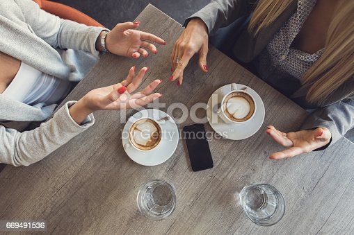 High angle view of two unrecognizable businesswomen communicating during coffee break in cafe.