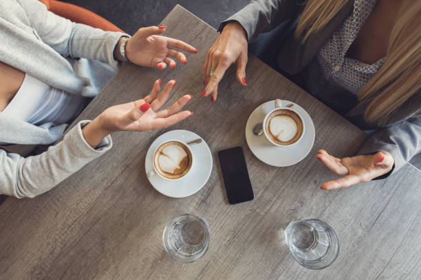 Above view of unrecognizable businesswomen discussing in a cafe. stock photo