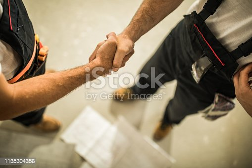 961745166istockphoto Above view of unrecognizable manual workers shaking hands on construction site. 1135304356