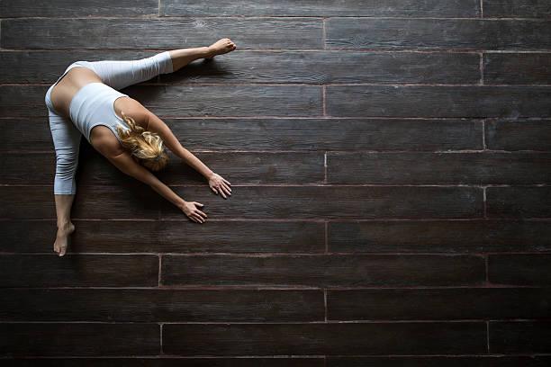 Vista de arriba de mujer haciendo ejercicios de relajación en el piso de madera. - foto de stock