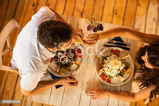 High angle view of couple having lunch at dinning table. Woman is feeding her boyfriend with toasted bread.