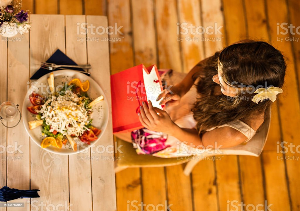 Above view of woman looking at shopping bag during lunch. foto de stock royalty-free