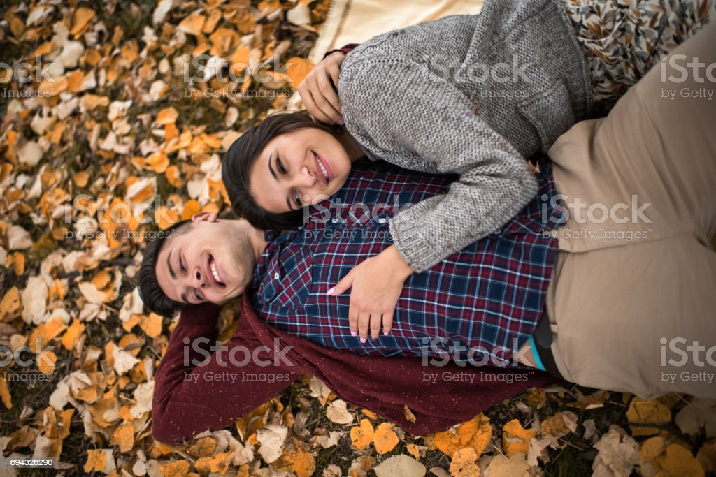 Above view of young couple in love relaxing in autumn leaves at the park. stock photo