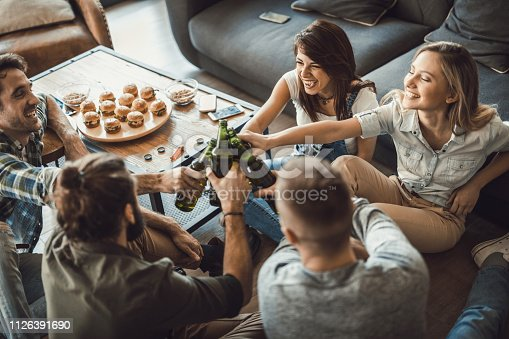 High angle view of happy friends having fun while toasting with beer at home.