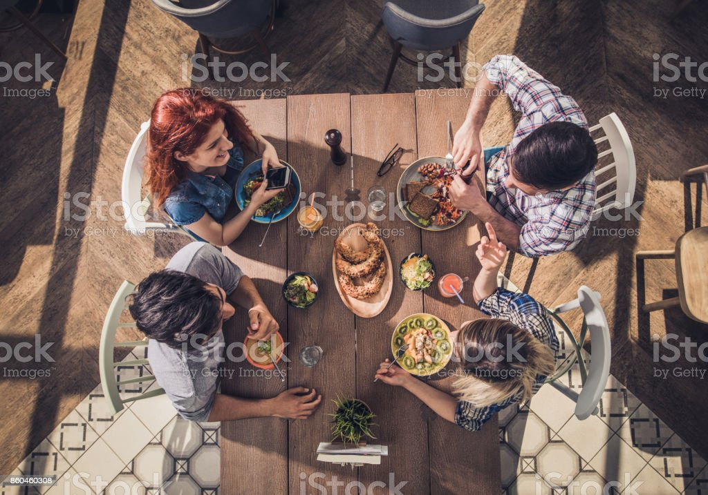 High angle view of four friends eating healthy food and communicating...