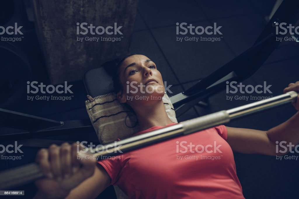Above view of young sportswoman exercising bench press in a gym. royalty-free stock photo