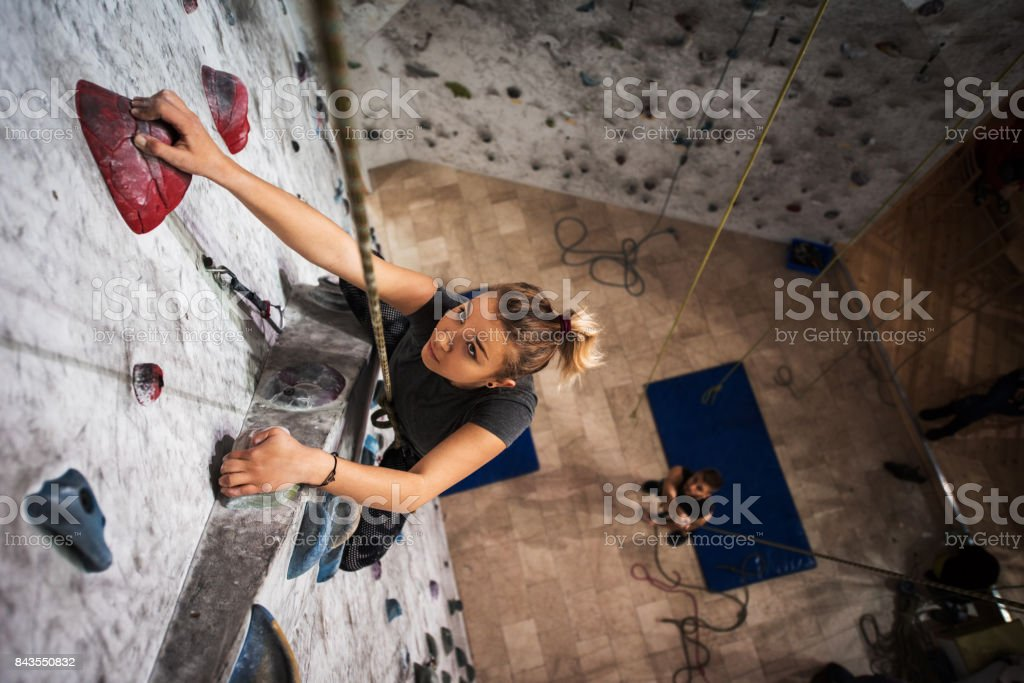 Above view of young woman exercising wall climbing in a gym. stock photo