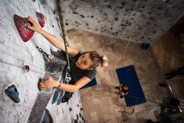 above view of young woman exercising wall climbing in a gym. - clambering stock photos and pictures