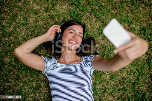 Above view of cute girl taking selfie and listening to music in the park