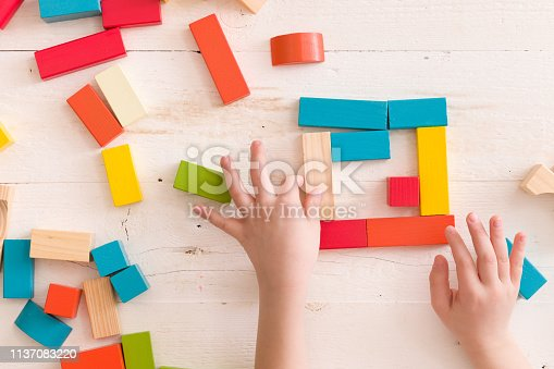 657779378 istock photo Above view on child's hands playing with wooden cubes on white wooden table background. 1137083220