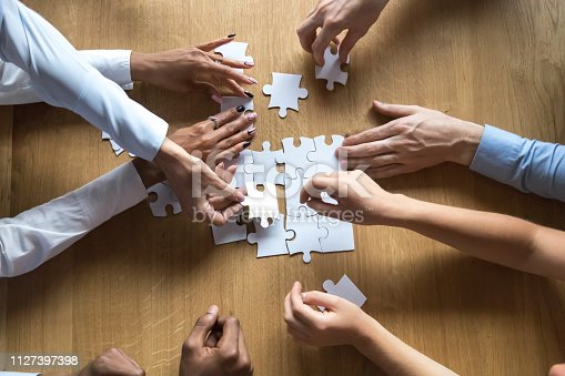 istock Above view people hands holding puzzle pieces 1127397398