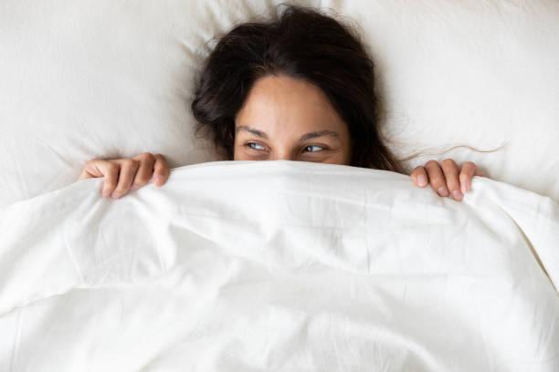 sopra vista giocosa giovane donna che nasconde il viso sotto la coperta - lenzuolo foto e immagini stock