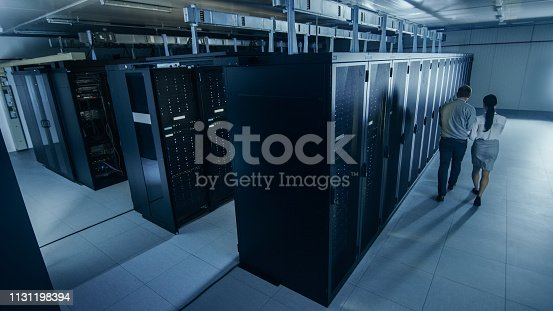 1131198396istockphoto Above Wide Shot of an IT Admin with a Laptop Computer and Young Technician Colleague Walking Next to Server Racks in Data Center. Running Diagnostics or Maintenance. 1131198394