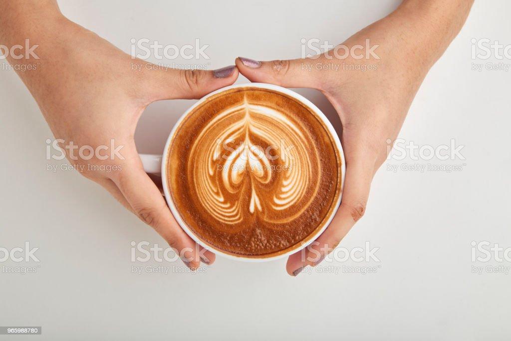 Ovanför kvinna hand innehav av kaffe Latte. - Royaltyfri Bord Bildbanksbilder