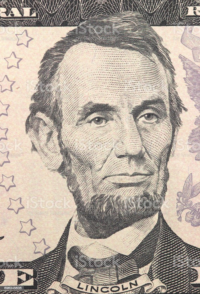 Abraham Lincoln face on US five or 5 dollars bill macro, united states money closeup. stock photo