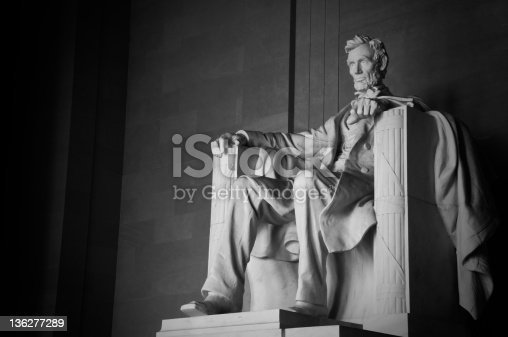 A monochrome image of the statue of Abraham Lincoln in the Lincoln in the Lincoln Memorial in Washington, DC.