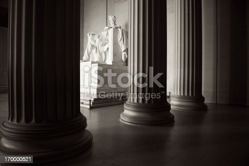 Statue of Abraham Lincoln in white marble seated beyond columns at the Lincoln Memorial in Washington DC