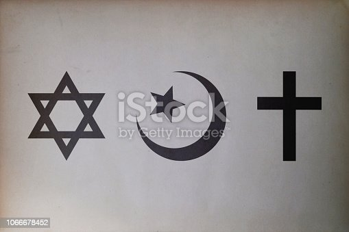 Close-up on Abrahamic symbols (Judaism, Islam and Christianity) printed on paper.