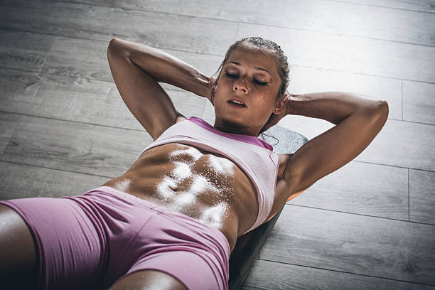 Abs Muscular woman doing sit-ups. abdominal muscle stock pictures, royalty-free photos & images