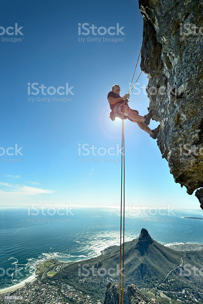 Abseiling climber over precipice looks up at rock face stock photo