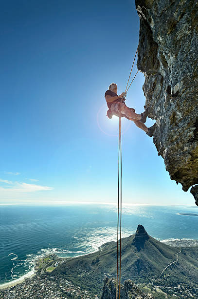 abseiling climber over precipice looks up at rock face - cape peninsula stock pictures, royalty-free photos & images