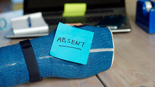Absent memo Absent  written on a memo that is stuck on a broken arm at the office absentee stock pictures, royalty-free photos & images