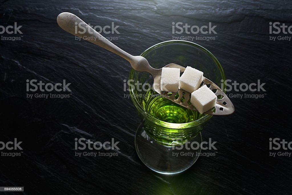 absinthe in pontarlier glass on dark slate stock photo