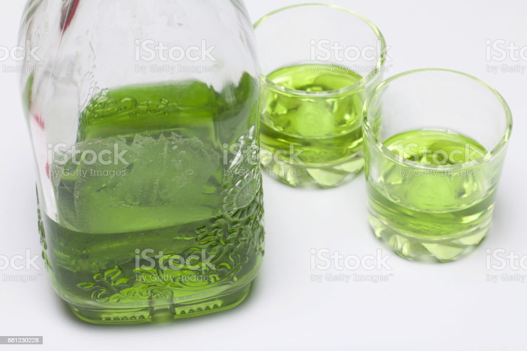 Absinthe is green. In a bottle and poured into glasses. On a white table-top. stock photo