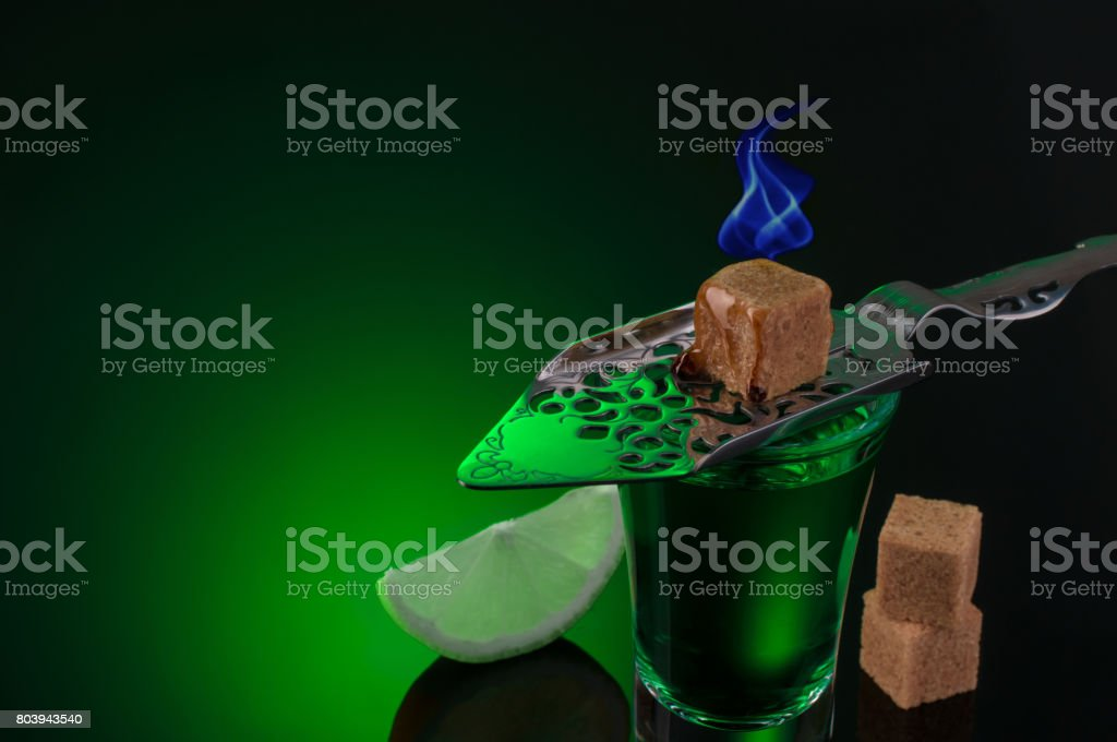 Absinthe shots with burning sugar and lime slices on dark background stock photo