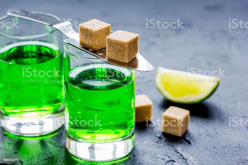 absinthe shots with lime slices and sugar on dark table background stock photo