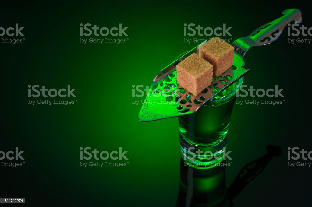 absinthe shots with spoon and sugar on dark stock photo
