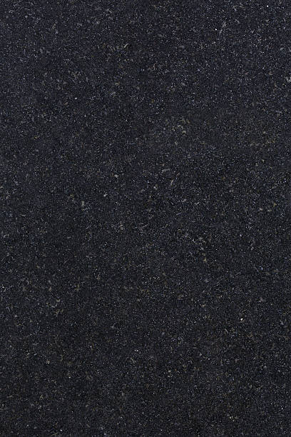 Absolute Black Granite a high definition view of Absolute Black  Granite (also known as Absolutto Black or Indian Black Granite) with its fine dense jet-black and silvery grains creating a very dark finish that is known to be very hard and durable. Originating from Southern India, this type of granite is used extensively for decorative purposes in kitchens, bathrooms, work tops, monuments, facades and also flooring. granite rock stock pictures, royalty-free photos & images