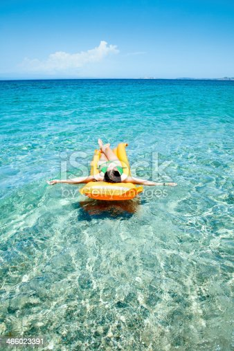Child enjoting absolute reax floating on pure turquoise waters.