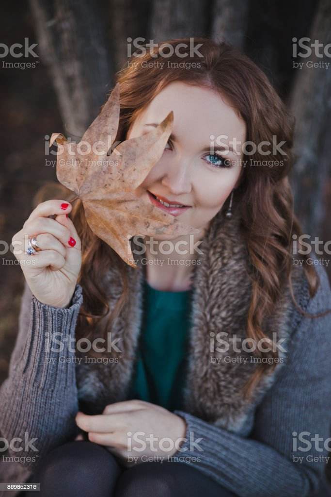 Absolutely beautiful lady woman with brunette hair deep blue eyes pink cheeks and rose pout lips sitting in autumn forest on foliage ground posing for camera portrait with leaf in hands stock photo