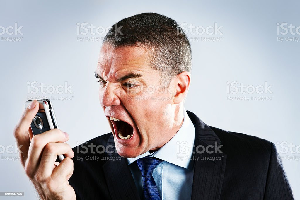 Absolutely furious businessman shouts into cell phone royalty-free stock photo