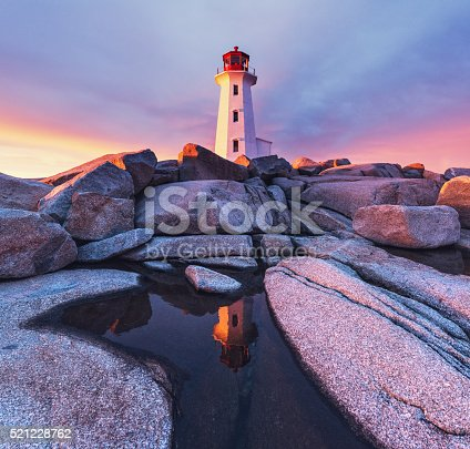 Peggy's Cove Lighthouse and the surrounding granite landscape absorb the rich colours of a Spring sunset.
