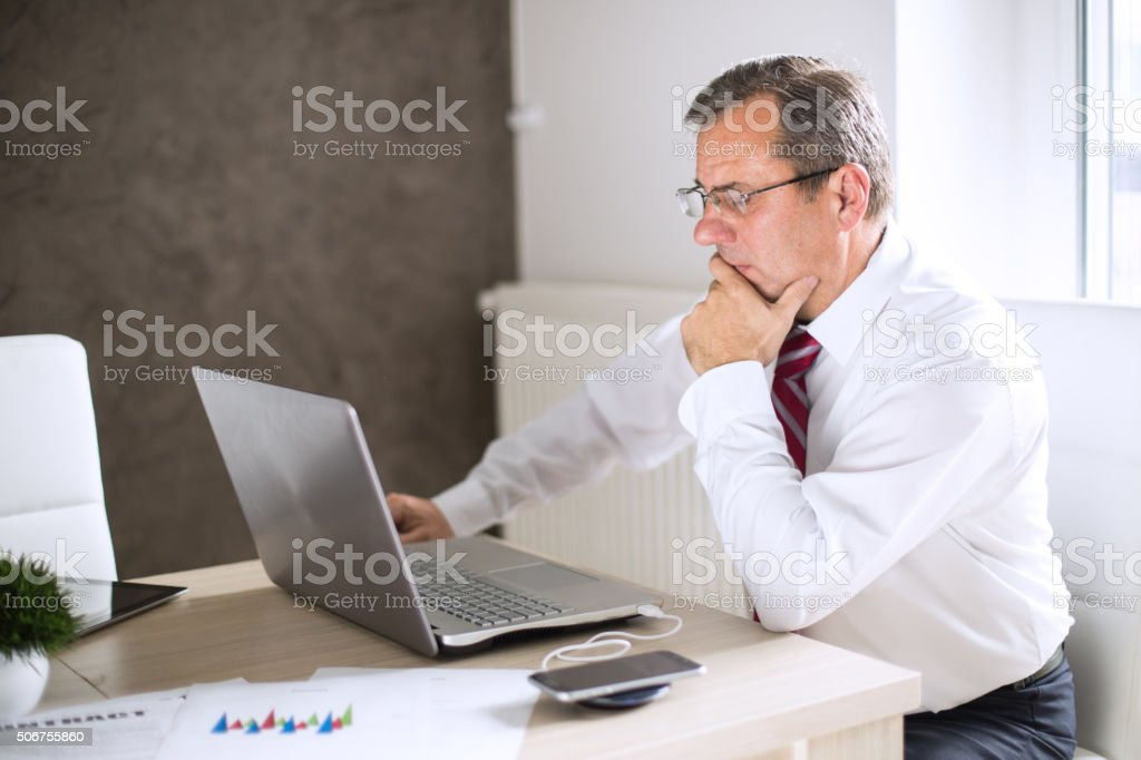 Absorbed pensive mature businessman stock photo