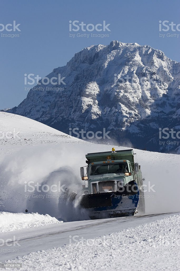 Absoroka mountains with snow plow and sanding truck in Yellowstone royalty-free stock photo