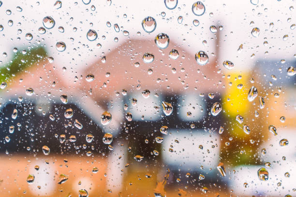 abstact image of defocused houses through a window with rain drops stock photo