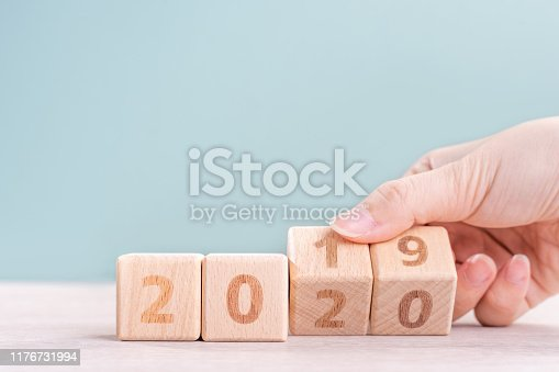 1054929988 istock photo Abstract 2020 & 2019 New year countdown design concept - woman holding wood blocks cubes on wooden table and green background. 1176731994