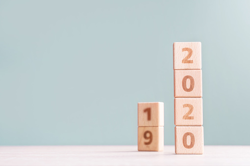 1163501702 istock photo Abstract 2020 & 2019 New year countdown design concept - wood blocks cubes on wooden table and low saturation green background. 1176676706