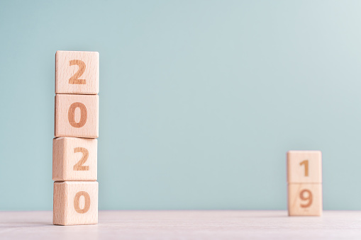 1163501702 istock photo Abstract 2020 & 2019 New year countdown design concept - wood blocks cubes on wooden table and low saturation green background. 1176676724