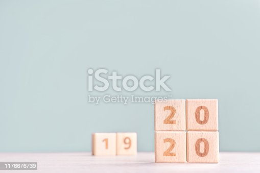 1054929988 istock photo Abstract 2020 & 2019 New year countdown design concept - wood blocks cubes on wooden table and low saturation green background. 1176676739